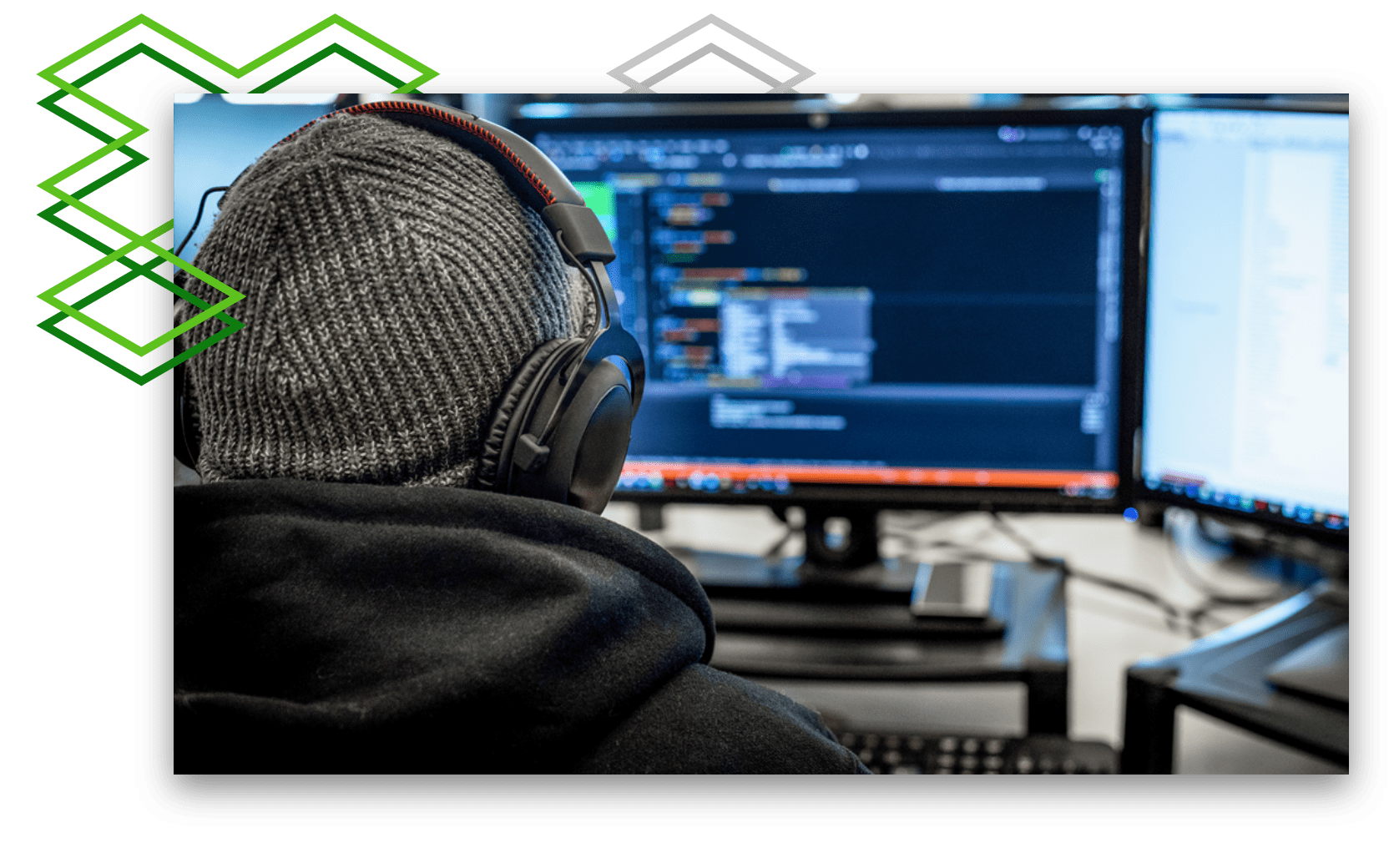 Person with headphones on over a beanie looking at a screen with code on it